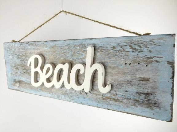 Rustic driftwood coastal sign