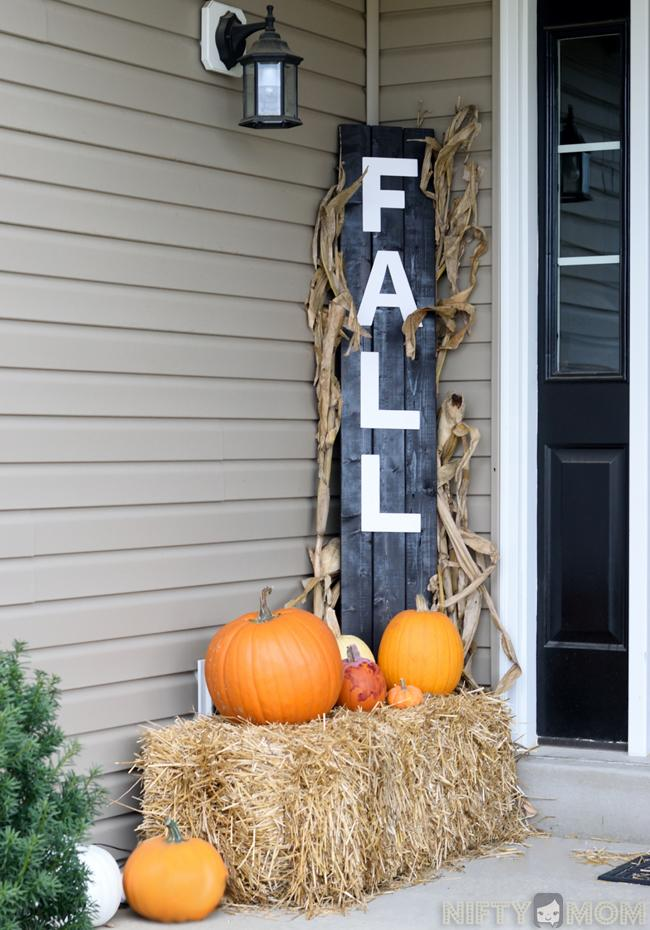 A Diy Fall Decoration With Hay Bales Pumpkins And Welcoming Wood Sign